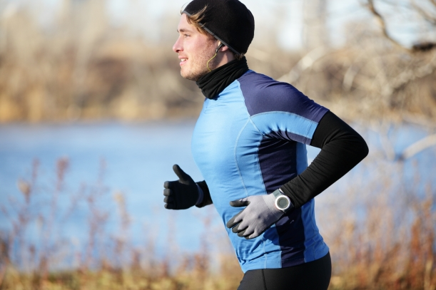 Runner man in fall running in autumn with gloves